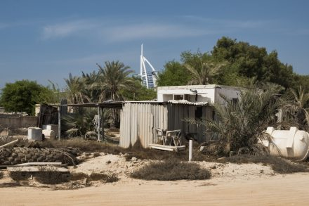 An old shack on a date plantation, with Dubai's Burj Al Arab hotel in the background