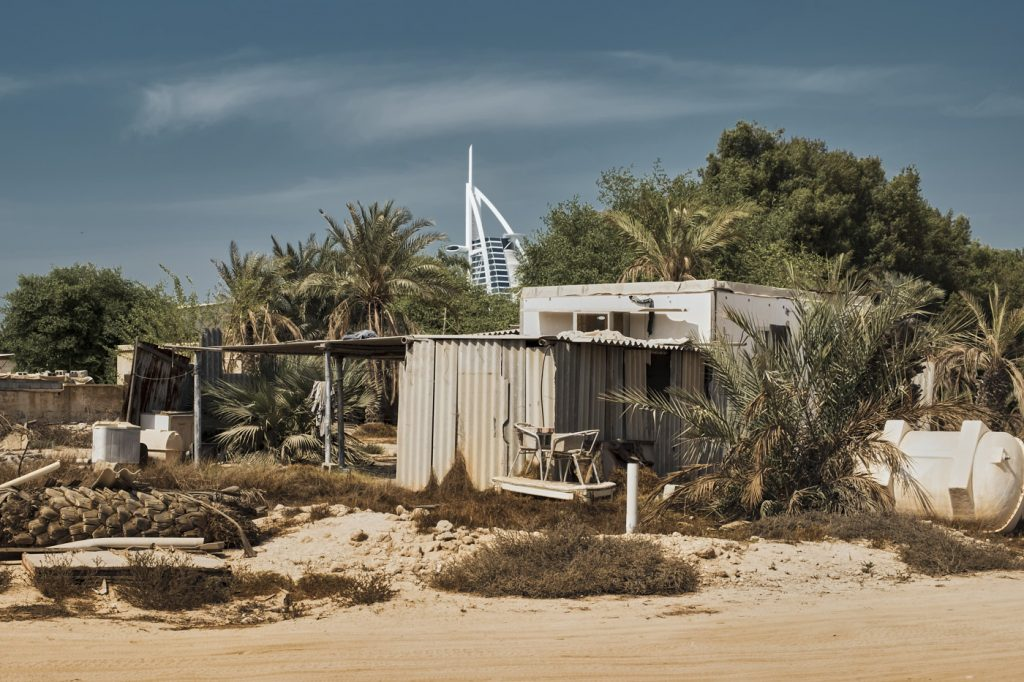 Image: Rich man, Poor man - an contrast of lifestyles in Dubai, UAE, showing a date farm worker accommodation cabin, with the luxury Burj Al Arab hotel in the background